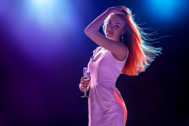 Conceito de festa, feriados, celebração, vida noturna e pessoas - sorrindo, linda jovem dançando