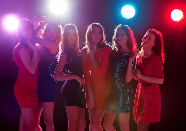Conceito de festa, feriados, celebração, vida noturna e pessoas - sorrindo, lindas garotas dançando