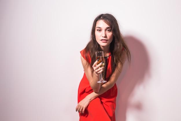 Conceito de festa, feriados e celebrações - jovem encantadora alegre no vestido vermelho, bebendo champanhe ou vinho e dançando sobre fundo branco.