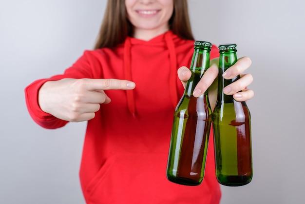 Conceito de festa. foto de close up recortada de um ponteiro positivo encantador e alegre demonstrando duas garrafas com álcool em uma parede cinza isolada