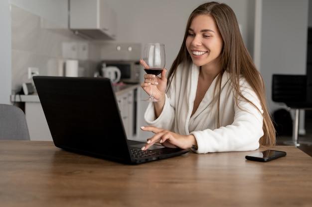 Conceito de festa online. bela jovem de aparência caucasiana se comunica por meio de conexão de vídeo via webcam