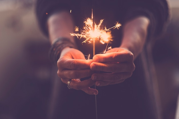 Conceito de festa, vida noturna e véspera de ano novo 2020 - close-up das mãos das pessoas com faíscas de fogo vermelho para celebrar a noite e o novo começo - filtro de cores quentes