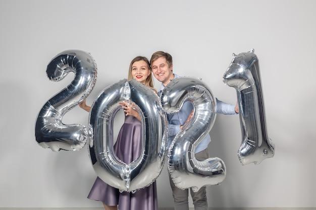 Conceito de festas, pessoas e feriados de ano novo - mulher e homem comemorando o ano novo de 2021