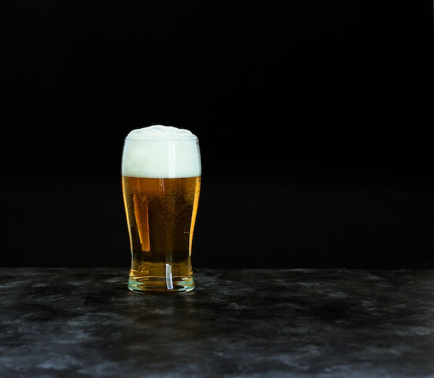 Conceito de festival de cerveja oktoberfest. cerveja gelada com espuma no vidro na obscuridade, copyspace.
