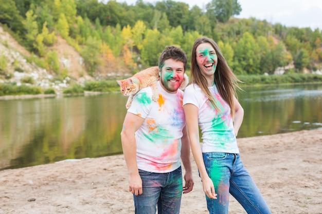 Conceito de festival holi, feriados, turismo, animal de estimação e natureza - retrato de mulher e homem com um gato coberto de poeira multicolorida.