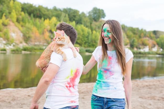 Conceito de festival holi, turismo e natureza - retrato de mulher e homem com um gato coberto de poeira multicolorida.