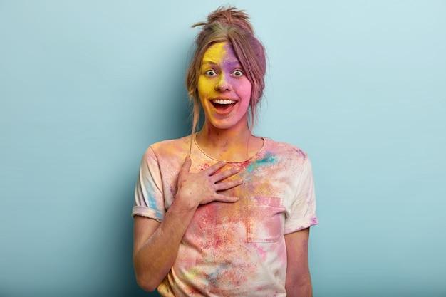 Conceito de festival indiano. linda mulher européia impressionada fica de mão no peito, olha de alegria, coberta de tintas coloridas, tem camiseta suja manchada, se diverte com as cores, isolado no azul