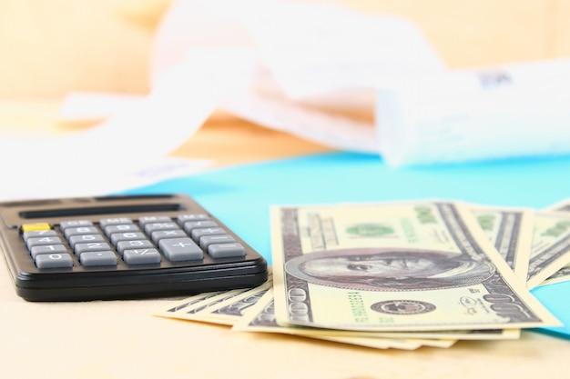 Conceito de finanças: as notas de cem dólares dos estados unidos, calculadora, contas.