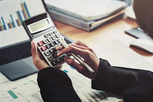 Conceito de finanças contábeis de negócios. contador usando calculadora para calcular com laptop trabalhando no escritório