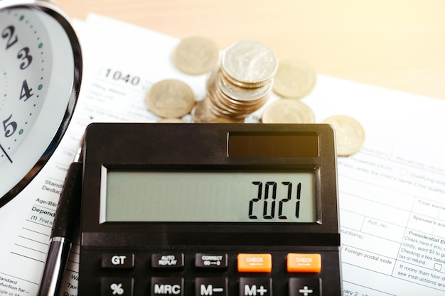 Conceito de finanças de negócios fiscais 2021. calculadora com dinheiro e formulário 1040 na mesa. pagamento anual de impostos