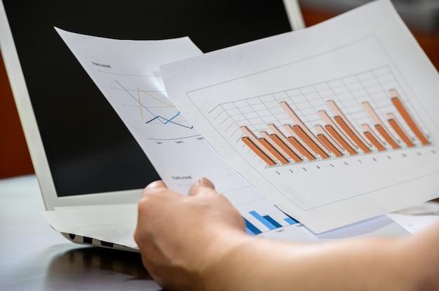 Conceito de finanças e negócios. a mão do empresário segurando o gráfico financeiro.