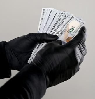Conceito de finanças. homem de luvas pretas segurando um pacote de dólares sobre um fundo cinza