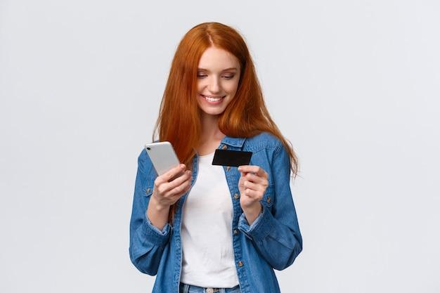 Conceito de finanças, negócios e educação. mulher ruiva atraente bonita alegre fazendo compra on-line, segurando o telefone e cartão de crédito, sorrindo como presente de compra para loja de internet para dia dos namorados