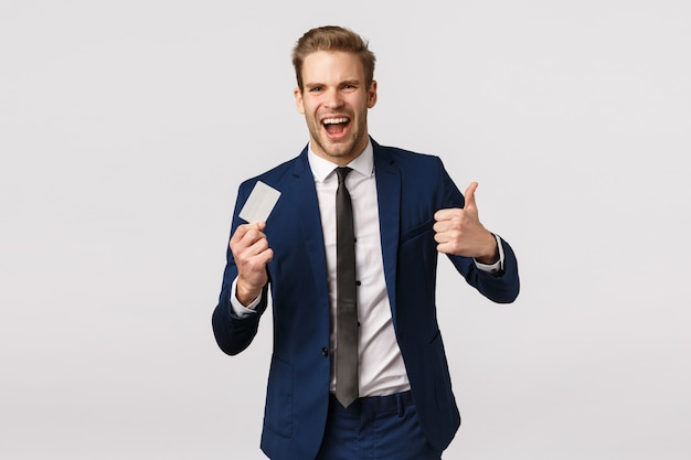 Conceito de finanças, negócios e riqueza. alegre e bonito jovem empresário loiro mostrando o polegar para cima em aprovação, como gesto de segurar o cartão de crédito, recomendar serviços bancários, fazer compra