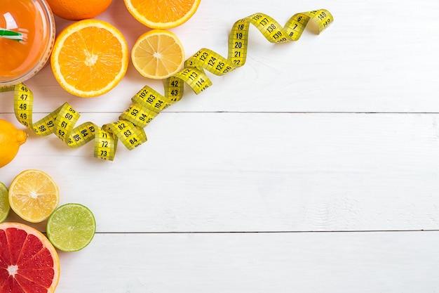 Conceito de fitness com frutas, um copo de suco e vista superior centímetro conceito de plano de fundo