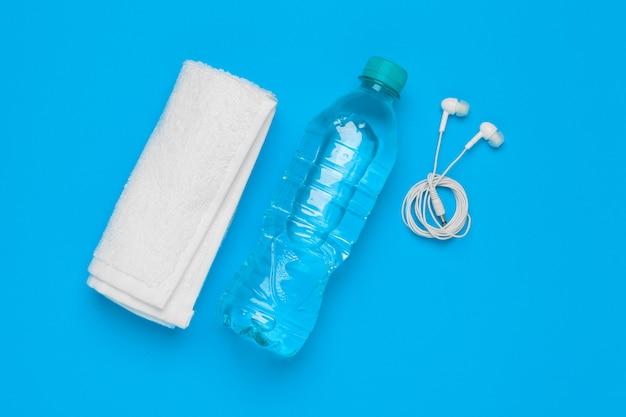 Conceito de fitness com garrafa de água, telefone celular com fones de ouvido