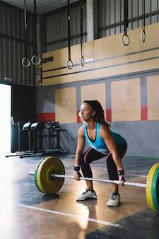 Conceito de fitness com mulher prestes a levantar barbell