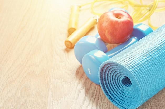 Conceito de fitness com um halteres azul e tapete de ioga, copie o espaço