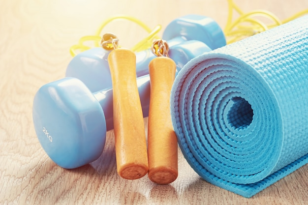 Conceito de fitness com um halteres azul, tapete de ioga e pular corda