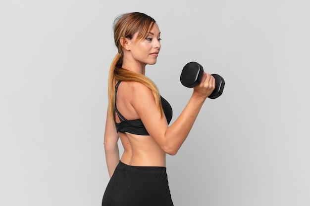 Conceito de fitness de mulher jovem e bonita levantando halteres