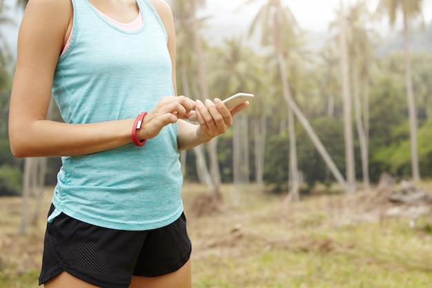 Conceito de fitness e estilo de vida. foto recortada de atleta feminina, tendo uma pausa durante o exercício de corrida, monitorando sua rota no celular.