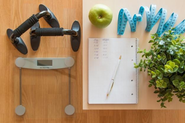 Conceito de fitness e perda de peso, balança e notebook em uma mesa de madeira, vista superior