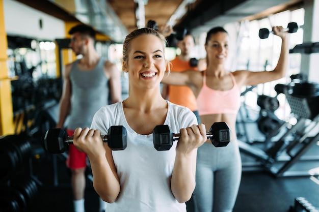 Conceito de fitness, esporte, exercício e estilo de vida saudável - grupo de pessoas felizes no ginásio