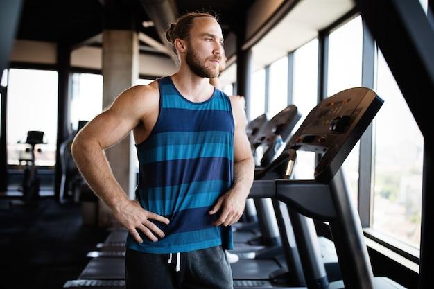 Conceito de fitness, esporte, exercício, treinamento e estilo de vida jovem apto homem malhando na academia