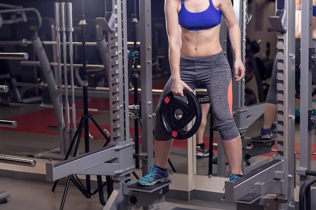 Conceito de fitness, esporte, treinamento, academia e estilo de vida. grupo de pessoas sorridentes exercitando na academia