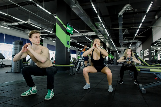 Conceito de fitness, esporte, treinamento, academia e estilo de vida - grupo de pessoas sorridentes, exercitando-se na academia, fazendo agachamentos