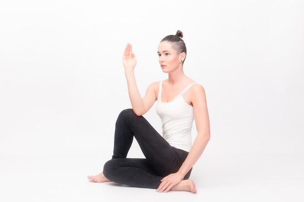 Conceito de fitness, esporte, treinamento e estilo de vida - jovem mulher fazendo exercícios de ioga. retrato de uma jovem linda em um sportswear branco fazendo ioga. mulher fazendo exercícios de alongamento Foto Premium