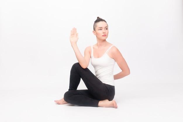 Conceito de fitness, esporte, treinamento e estilo de vida - jovem mulher fazendo exercícios de ioga. retrato de uma jovem linda em um sportswear branco fazendo ioga. mulher fazendo exercícios de alongamento