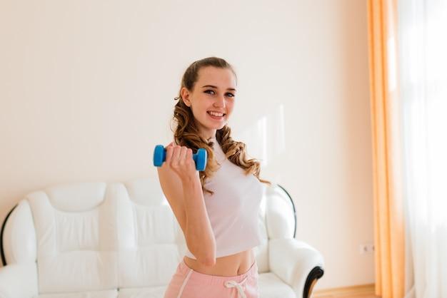 Conceito de fitness, esporte, treinamento e estilo de vida - mulher sorridente treinando em casa