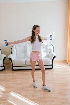 Conceito de fitness, esporte, treinamento e estilo de vida, mulher sorridente treinando em sua casa