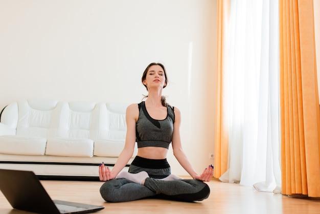 Conceito de fitness, esporte, treinamento e estilo de vida - mulher sorridente treinando em sua casa