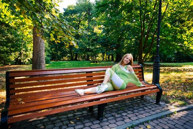 Conceito de fitness, esporte, treinamento, parque e estilo de vida - mulher afro-americana sorridente fazendo flexões no banco ao ar livre