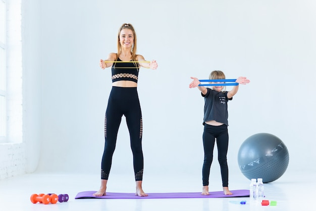 Conceito de fitness, esporte, treinamento, pessoas e estilo de vida - mulher fazendo exercícios com expansor ou banda de resistência no ginásio