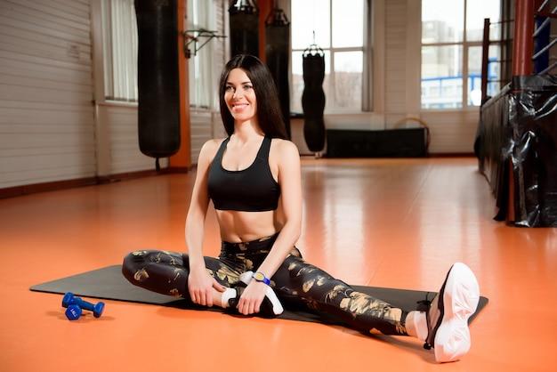 Conceito de fitness, esporte, treino, academia e estilo de vida - jovem se alongando na academia