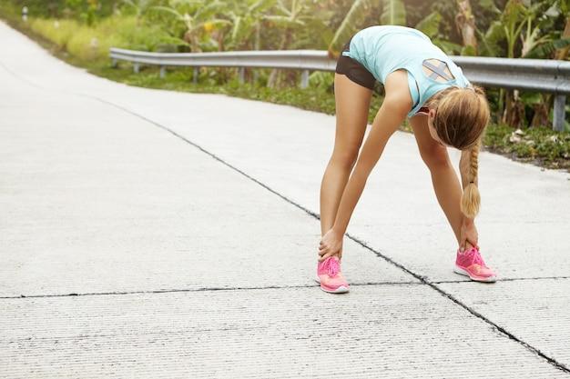 Conceito de fitness, esportes, exercícios, pessoas e estilo de vida. atleta de mulher loira alongando e curvando-se antes de correr ao ar livre de treino.