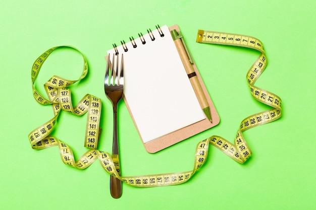 Conceito de fitness, fita métrica com garfo e notebook