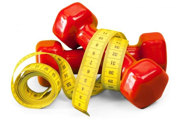 Conceito de fitness. halteres e fita métrica.