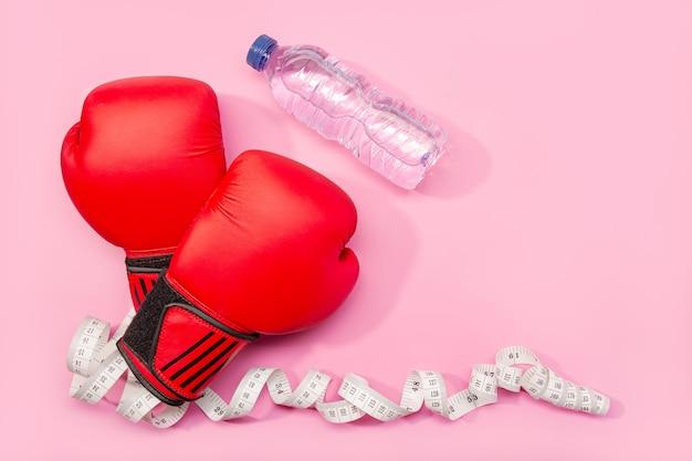 Conceito de fitness, perda de peso ou exercício. luvas de boxe, água mineral e fita métrica isolada