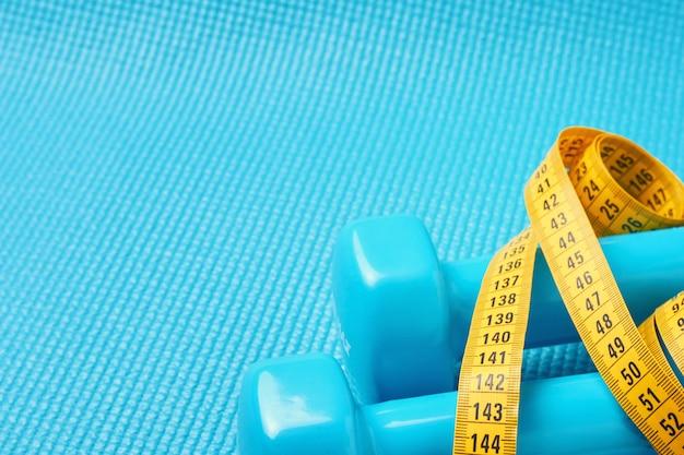Conceito de fitness. pesos e fita métrica em um fundo azul com espaço da cópia.