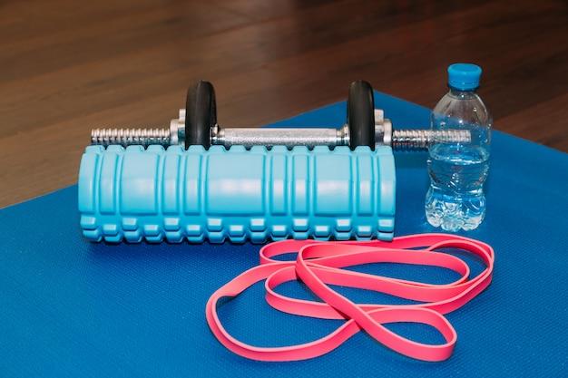 Conceito de fitness - tapete de ioga, halteres, pular corda, garrafa de água e fita métrica