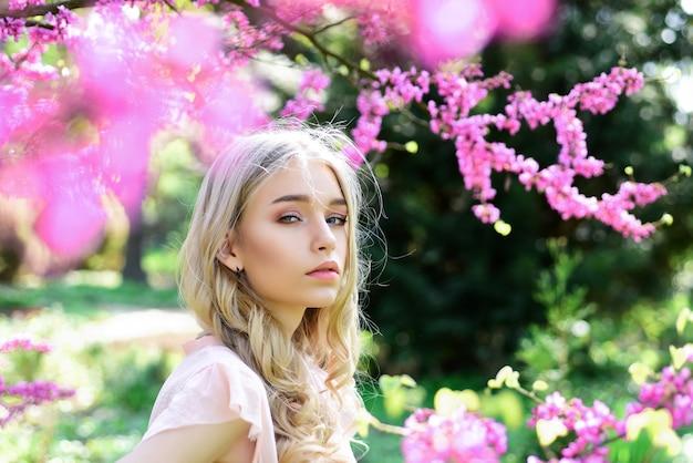 Conceito de flor de primavera. lindo rosto feminino com pele perfeita. menina com rosto sonhador, loira macia perto de flores violetas da árvore de judas, plano de fundo da natureza. linda jovem primavera