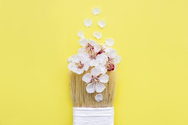 Conceito de flor de primavera. pincel com flor de damasco em fundo amarelo.