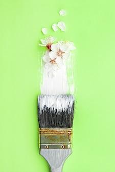 Conceito de flor de primavera. pincel com flor de damasco sobre fundo verde.