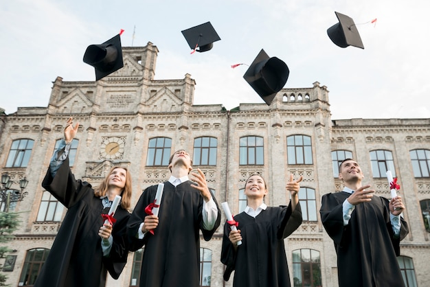 Conceito de formatura com estudante jogando chapéus no ar
