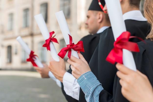 Conceito de formatura com estudantes segurando seus diplomas