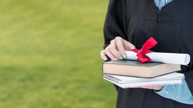 Conceito de formatura com o aluno segurando o livro e diploma